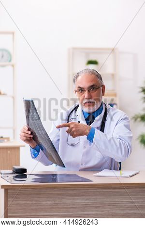 Old male doctor radiologist working in the hospital