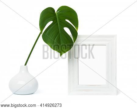 White wooden shabby chic picture frame for A4 or A5 formats mockup with monstera leaf in vase on white background. Blank image area masked with clipping path.
