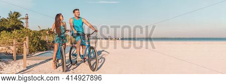 Florida beach vacation couple biking sport rental bikes recreational activity happy watching sunset on Sanibel Island by the Lighthouse. Young woman and man riding bicycles. Summer people lifestyle.