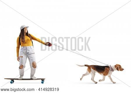 Full length shot of a female skater riding a longboard with a dog on a lead isolated on white background