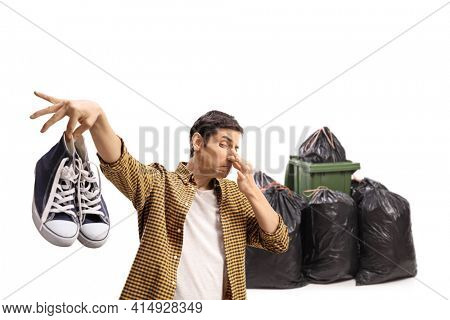 Guy throwing a pair of smelly trainers in garbage isolated on white background