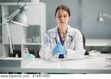 Portrait Of A Medical Specialist In The Workplace. A Female Doctor In Medical Gloves In The Office O