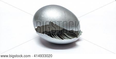 Closeup Of Broken Silver Egg Shell Isolated In A White Background With A Selective Focus . Symbolizi