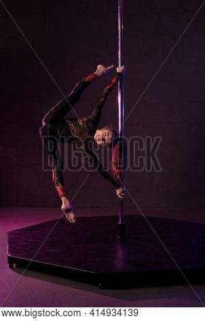 Graceful Teem Girl Doing Gymnastic Split On Pole In Darkness