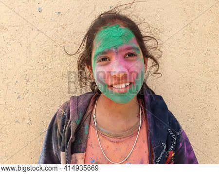 Close Up Of An Indian Kid Girl With Multi Colored Holi Powder On His Face, A Little Girl Celebrating