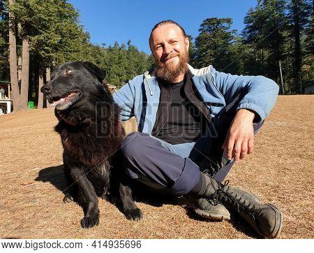 Ukrainian Man Sitting With Black Dog In Nature