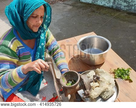 Concept Of Authentic Living, A Indian Woman With Traditional Clothes Grind Wet Urad Dal (black Gram)