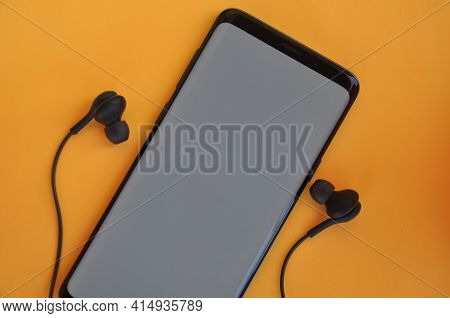 High Angle Shot Of A Black Smartphone With A Blank White Screen With Black Earphones On A Yellow Bac