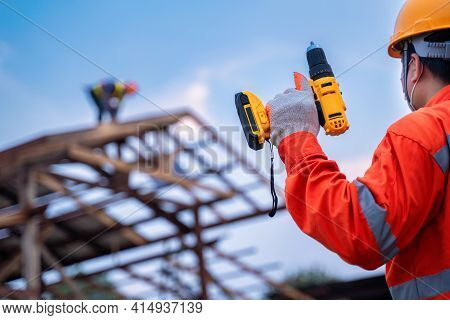 Roofing Tools, Roofer Worker Holding Electric Drill Used On New Roofs With Metal Sheet At Constructi