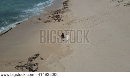 Young Female Surfer Sitting On The Beach Looking Thinking To Go Surf At The Waves Of The Rolling Pac