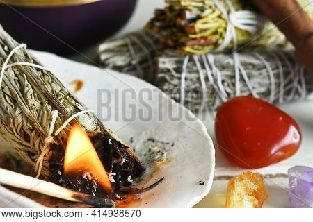 A Close Up Image Of A Burning White Sage Smudge Bundle And Several Healing Energy Crystals.