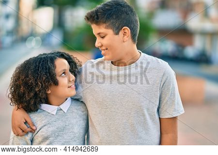 Adorable latin brother and sister hugging at the park.