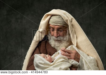 Simeon holding Baby Jesus in his arms against a dark background