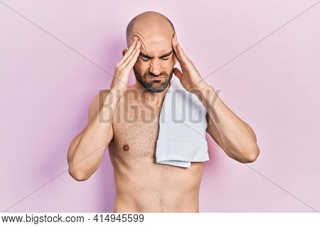 Young bald man standing shirtless with hand on head, headache because stress. suffering migraine.