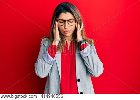 Beautiful brunette woman wearing business shirt and glasses with hand on head, headache because stress. suffering migraine.