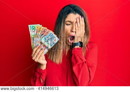 Beautiful brunette woman holding australian dollars yawning tired covering half face, eye and mouth with hand. face hurts in pain.