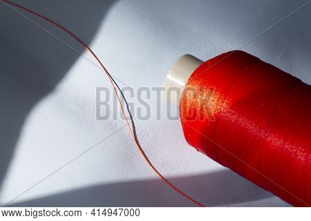 A Spool Of Red Thread On A Blue Leather. Sewing Thread. Shoe Industry