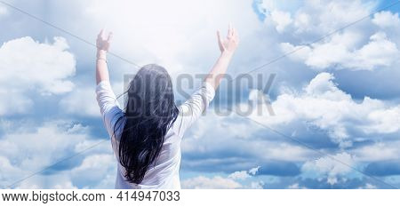 Young Girl With Raised Arms. Against A Background Of Blue Sky And Clouds. Joy. Prayer And Worship To