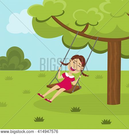 Cute Smiling Girl On A Tree Swing In The Park. Happy Swinging Kid Playing In The Backyard. Child Enj