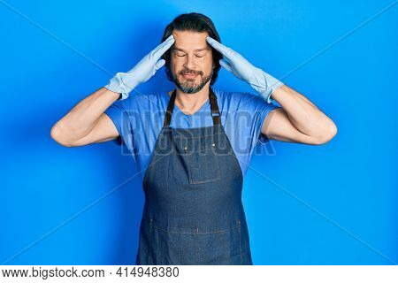 Middle age caucasian man wearing cleaner apron and gloves with hand on head, headache because stress. suffering migraine.