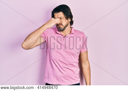 Middle age caucasian man wearing casual white t shirt smelling something stinky and disgusting, intolerable smell, holding breath with fingers on nose. bad smell
