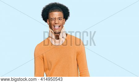 African american man with afro hair wearing cervical neck collar winking looking at the camera with sexy expression, cheerful and happy face.