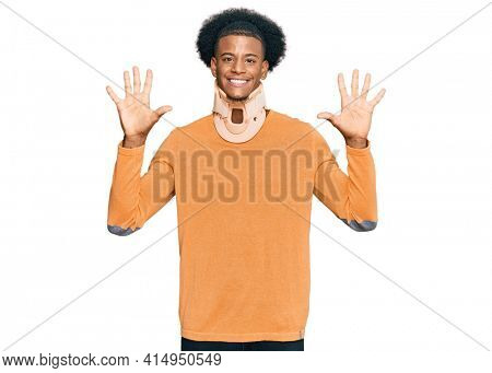 African american man with afro hair wearing cervical neck collar showing and pointing up with fingers number ten while smiling confident and happy.