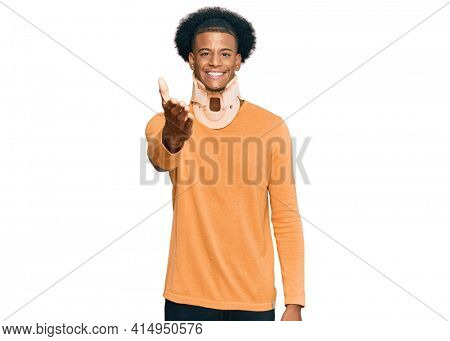 African american man with afro hair wearing cervical neck collar smiling friendly offering handshake as greeting and welcoming. successful business.