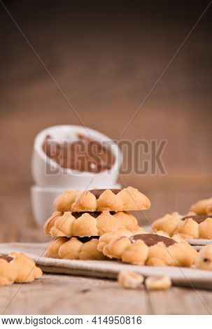 Flower Shaped Chocolate Biscuits On Wooden Table.