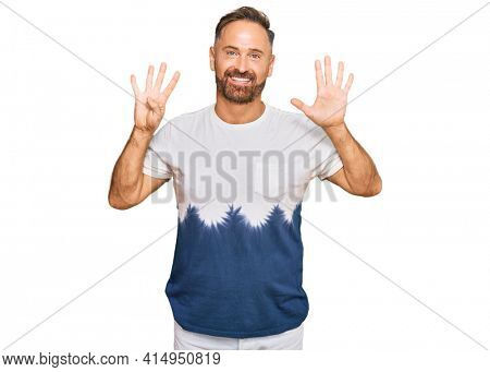 Handsome middle age man wearing casual tie dye tshirt showing and pointing up with fingers number nine while smiling confident and happy.