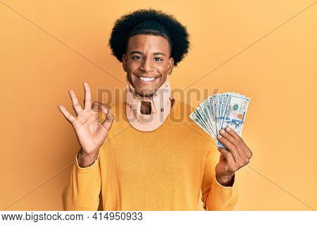 African american man with afro hair wearing cervical neck collar and holding money from insurance doing ok sign with fingers, smiling friendly gesturing excellent symbol