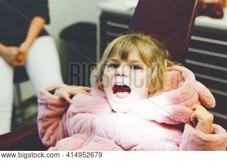 Cute Little Toddler Girl Sitting With Open Mounth At The Dentist. Happy Brave Child Waiting For Trea