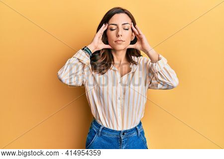 Young brunette woman wearing casual clothes over yellow background with hand on head, headache because stress. suffering migraine.