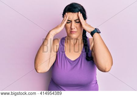 Plus size brunette woman wearing sportswear with hand on head, headache because stress. suffering migraine.