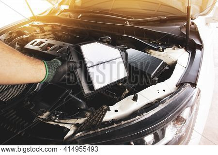 Mechanic Hand Is Replacement Car Air Filter Into The Filter Socket Of A Car Engine With A Sunlight