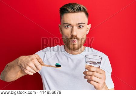 Young redhead man holding toothbrush with toothpaste and glass of water making fish face with mouth and squinting eyes, crazy and comical.
