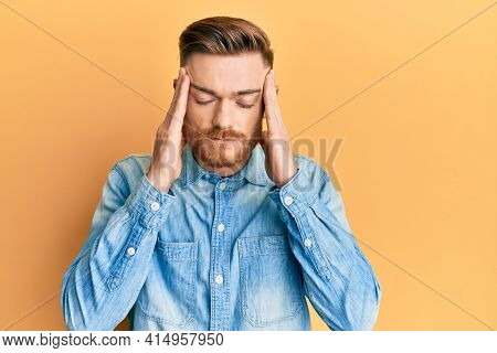 Young redhead man wearing casual denim shirt with hand on head, headache because stress. suffering migraine.