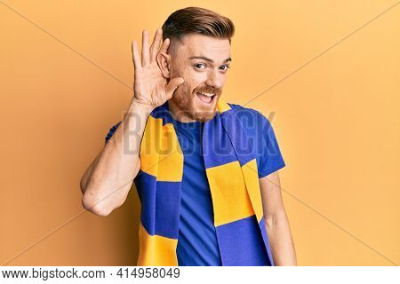 Young redhead man football hooligan cheering game smiling with hand over ear listening and hearing to rumor or gossip. deafness concept.