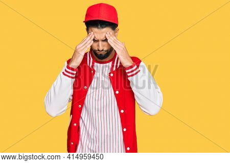 Young man with beard wearing baseball uniform with hand on head for pain in head because stress. suffering migraine.