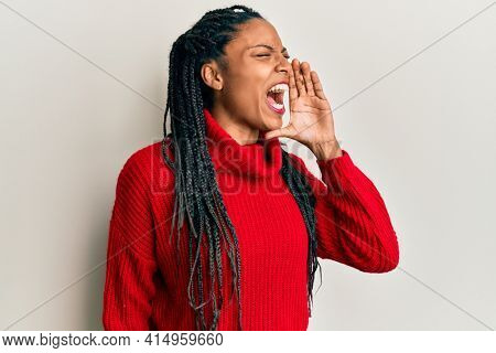 African american woman wearing casual winter sweater shouting and screaming loud to side with hand on mouth. communication concept.