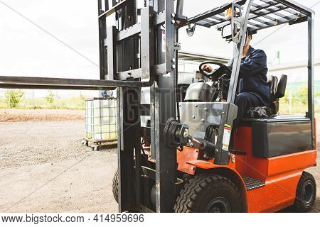 A Man On A Forklift Works In A Large Warehouse, Unloads Bags Of Raw Materials