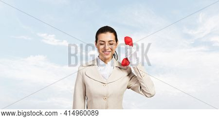 Young Business Woman Holding Red Retro Phone With Closed Eyes. Call Center Operator In White Busines