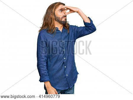 Attractive man with long hair and beard wearing casual clothes smelling something stinky and disgusting, intolerable smell, holding breath with fingers on nose. bad smell