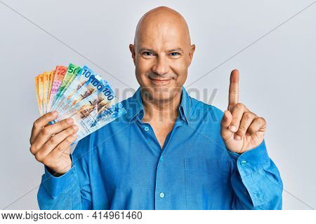 Middle age bald man holding swiss franc banknotes smiling with an idea or question pointing finger with happy face, number one