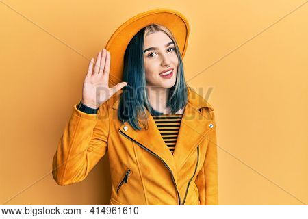 Young modern girl wearing yellow hat and leather jacket waiving saying hello happy and smiling, friendly welcome gesture