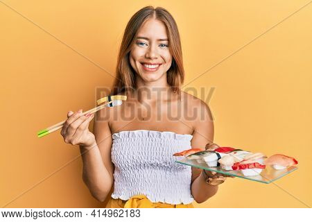 Beautiful young blonde woman eating omelette sushi using chopsticks smiling with a happy and cool smile on face. showing teeth.