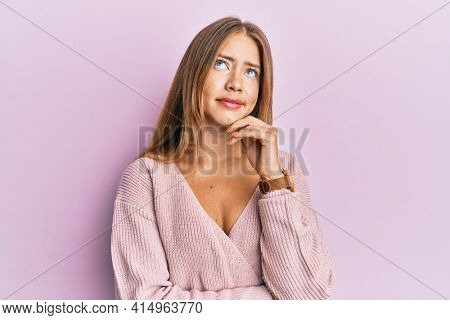 Beautiful young blonde woman wearing casual pink sweater thinking concentrated about doubt with finger on chin and looking up wondering