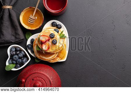 Healthy breakfast with pancakes and herbal tea. Homemade american pancakes with berries and honey. Top view flat lay with copy space