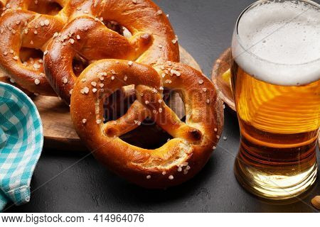 Lager beer mug and fresh baked homemade pretzel with sea salt on stone table. Classic beer snack