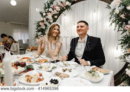 Wedding Couple At The Table Rejoices The Holiday. The Newlyweds Are Happy Sitting At The Festive Tab